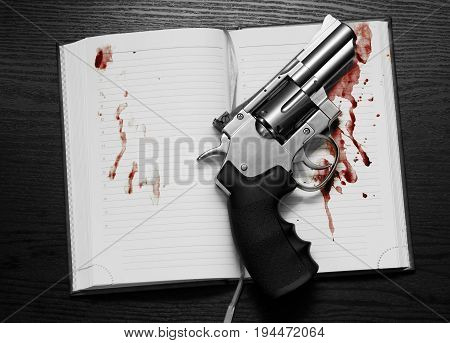 Revolver and a open notebook in blood on the table