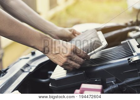 Technician holding dirty air filter for car maintenance and repair concept