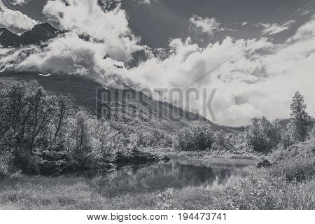 Beautiful Nature Norway mountains landscape with clouds Scandinavia. Black and white foto.