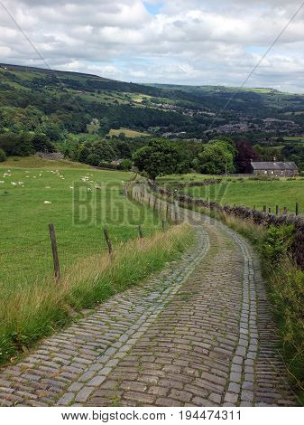 winding stone cobbled lane running downhill in farmland with sheep grazing farm buildings woods yorkshire moorland and pennine villages with a dramatic cloudy sky.