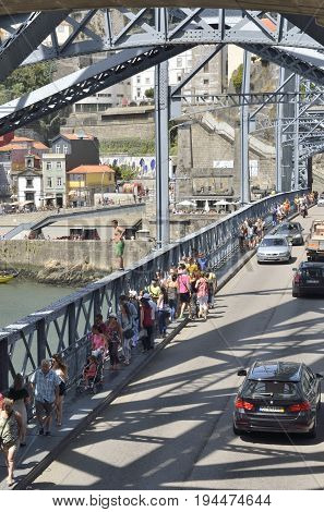 PORTO, PORTUGAL - AUGUST 7, 2015: Young man at the handrail of the bridge Dom Luis ready to jump to the Douro River in Porto Portugal.
