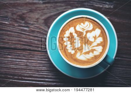 Top view image of hot latte coffee with latte art in blue coffee cup on vintage wooden table