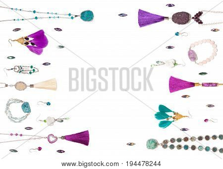 Handmade turquoise and violet bijouterie with gems, tassels and feathers, lying flat on the white horizontal background with central empty place for text, top view
