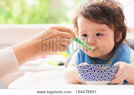 Happy little baby boy being fed by his mother