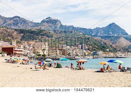 People On Sand Beach In Giardini Naxos Town