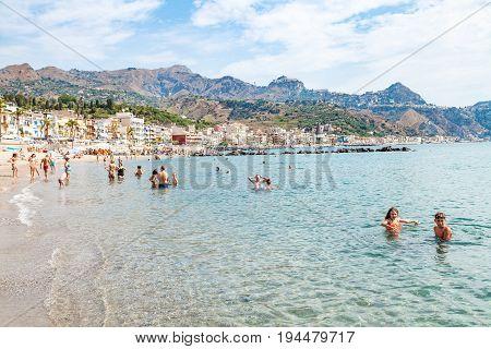 People In Sea Near Waterfront Of Giardini Naxos
