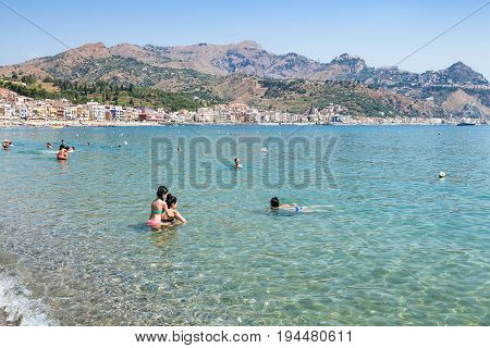 Tourists In Ionian Sea On Beach In Giardini Naxos
