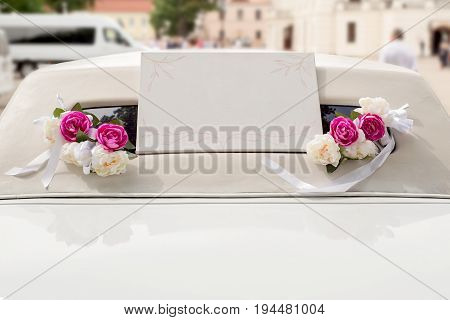 White wedding limousine decorated with red and white flowers