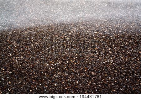 Dark sand and sea wave long exposure abstract textural background