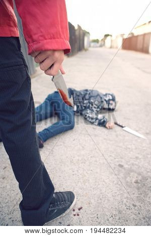 Man standing next to stabbed man lying on ground