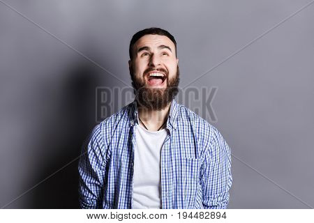 Portrait of angry crying bearded man. Aggressive guy screaming loudly, looking upwards, gray studio background. Psychotherapy exercise