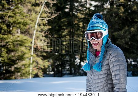 Woman in Toque and Ski Goggles Laughs at Camera in winter forest