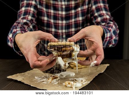 Womans Hands Hold a Gooey Marshmallow Smore with dripping melted marshmallow