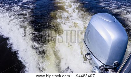 Outboard motor. Summer river landscape, photographed from the side of the boat