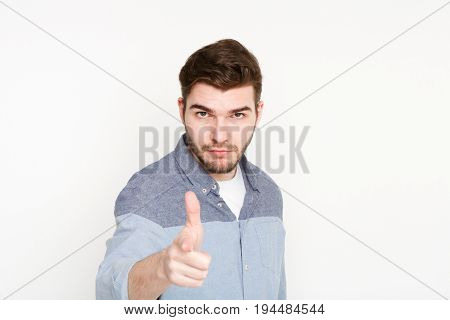 Strict serious young man point with index finger on camera, white isolated studio background. Motivation poster