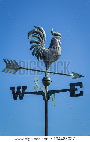 Weather vane, wind vane, weathercock, showing direction of the wind against clear blue sky, vertical
