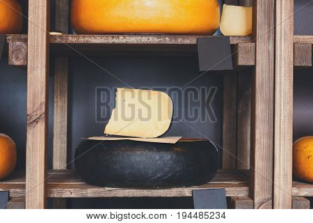 Parmesan cheese as wheel and piece on grocery shop wooden shelf, closeup
