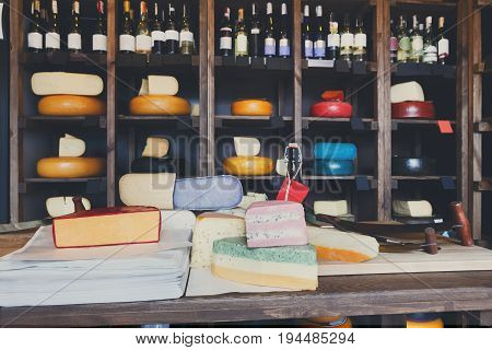Grocery shop interior. Cheese wheels arranged on wooden shelves, coloured cheese and wrapping paper on counter and wine assortment, background
