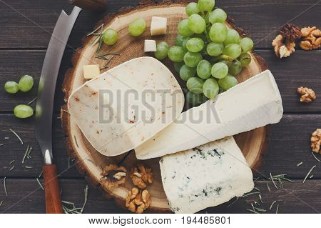 Cheese platter, blue roquefort and gouda herb on natural wood disc with grapes and nuts, still life, top view