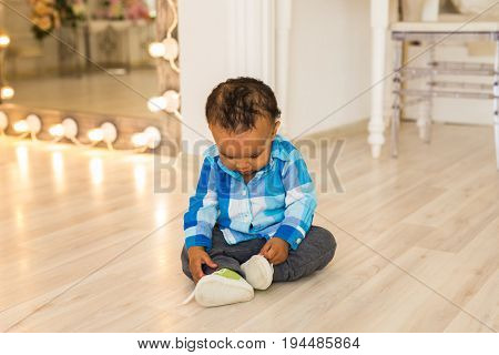 Small child tries to put on his shoes. Mixed race baby boy with shoes.