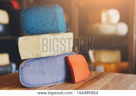 Cheese shop assortment. Gouda pesto lavender, blue, violet and red at cheese grocery background