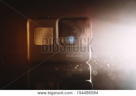 Kharkov, Ukraine - April 13, 2017: GoPro HERO 5 digital action camera in spotlight with lensflare on black. Compact gadget waterproof , support 4k video and is often used in extreme photography