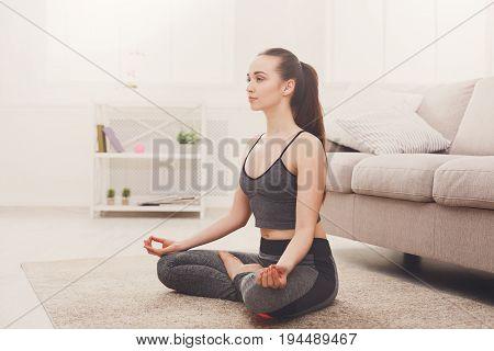 Yoga at home, woman do meditation lotus pose, Padmasana asana. Young girl exercise