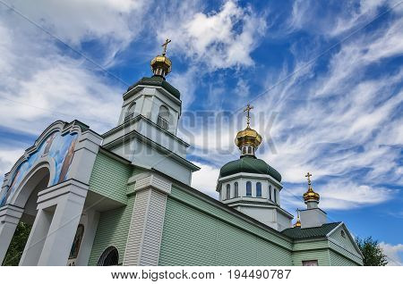 Christian temple and golden domes against the sky with clouds.