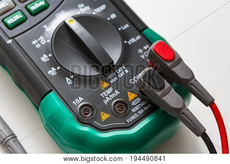 Digital multimeter with switch and wires. Measurement electrician tool closeup on white background