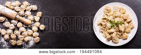 Plate of traditional russian pelmeni ravioli or dumplings on black background top view
