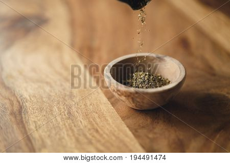 dried provence herb mix falling in wood bowl for seasoning on table, shallow focus