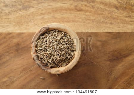 cumin zira seeds in wood bowl on table from above, shallow focus
