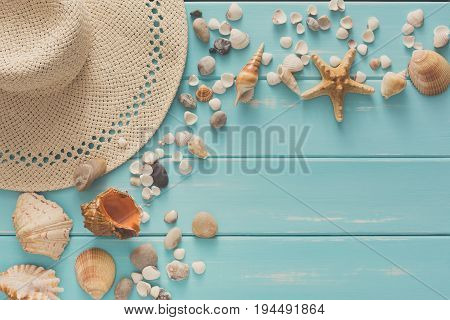 Vacation background on blue wood, top view with copy space. Beach pebbles, seashells and straw hat