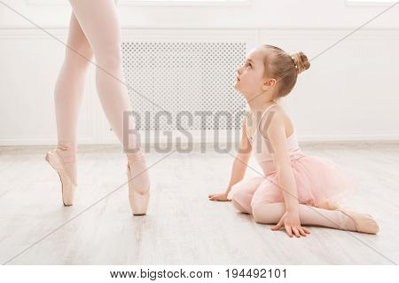 Little girl looking at professional ballet dancer. Cute baby dreaming to become ballerina, copy space. Classical dance school background, practicing for children