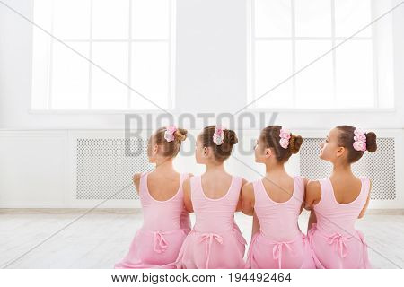 Little ballerinas in ballet studio. Group of girls having break in practice, sitting on floor, back view. Classical dance school