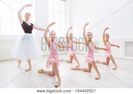 Young ballet teacher and students ballerinas in choreography class of ballet school.