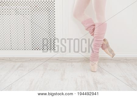 Legs of ballet dancer wearing gaiters closeup. Young ballerina preparing for practicing in classical dance school, using special cloth