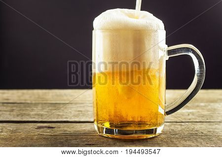 Pouring beer into a glass on a wooden table. Alcoholic beverages. Alcohol-free beer. Sale of beer to the bar