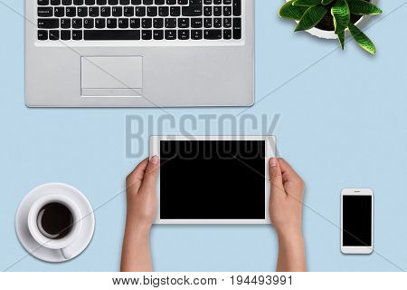 Woman`s Hands Holding Modern Tablet Over Blue Background. Office Desk With Laptop Computer, Flower,