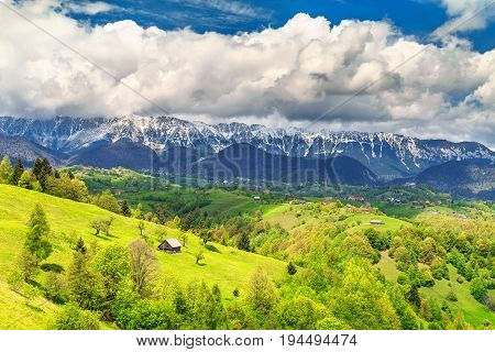 Amazing alpine landscape with stunning green fields and high snowy Piatra Craiului mountains near Brasov Transylvania Romania Europe