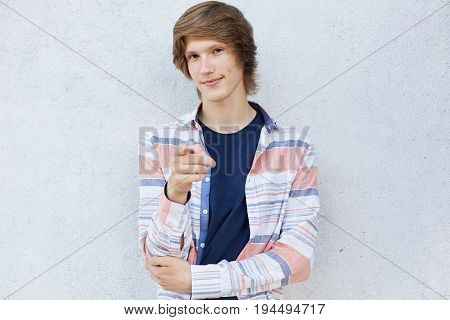 Trendy Male With Stylish Haircut Wearing Casual Shirt Pointing With Finger At Camera Having Shy Look