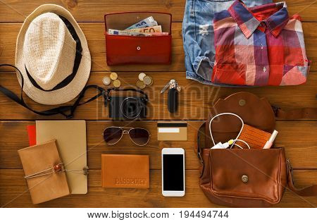 Journey planning, tourist essentials set top view. Preparing for travel, flat lay of traveller baggage, blank smartphone screen, copy space