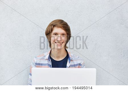 Smiling Teenage Boy With Attractive Appearance Sitting Over White Background Using Laptop For Watchi