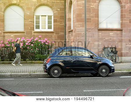 STRASBOURG FRANCE - MAY 30 2017: Blue Fiat 500 Riva parked in the city with nearby passing senior man admiring the beautiful car. This is a special edition of the facelift Fiat 500 that showcases the Riva yacht brand which is owned by the Ferretti Group.