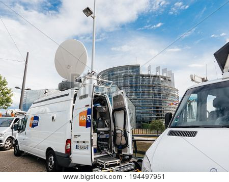 STRASBOURG FRANCE - JUN 30 2017: Via storia TV Media Television Trucks with multiple Satellite parabolic antennas and fiber optic cables preparing to report live the official European Ceremony of Honour for Dr. Helmut Kohl at European Parliament