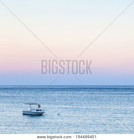 View Of Boat In Sea In Blue And Pink Twilight