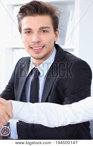 Businessman looking at camera while partners shaking hands at meeting