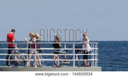 KOLOBRZEG, WEST POMERANIAN / POLAND - 2017: Holiday guests of the resort walk the pier