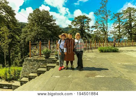 Thimphu Bhutan - September 10 2016: Tourists posing with Bhutanese guide at the Druk Wangyal Lhakhang Temple Dochula Pass Bhutan. Dochula pass is located on the way to Punakha from Thimphu.