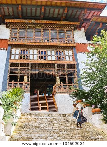 Paro Bhutan - September 10 2016: Low angle view of an old temple stairs. Bhutanese man and woman descending the temple stairs.